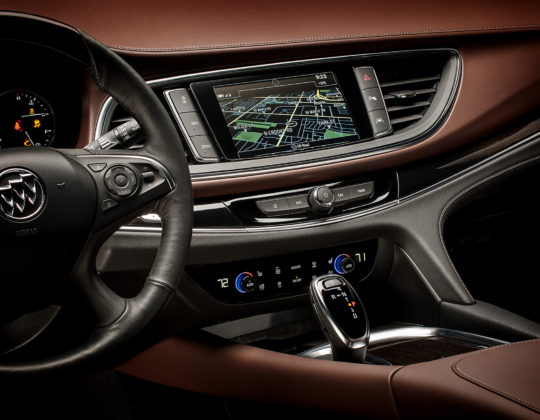 Model year 2018 Buick Enclave Avenir front cockpit.2018 Buick Enclave Avenir front cockpit, drivers POV featuring center stack with touch screen navigation, climate and entertainment controls, gear shift and surround, steering wheel with chestnut leather dash.2018 Buick Enclave Avenir front cockpit, drivers POV featuring center stack with touch screen navigation, climate and entertainment controls, gear shift and surround, steering wheel with chestnut leather dash.