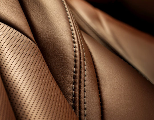 Model year 2018 Buick LaCrosse Avenir premium chestnut leather seat back stitch detail.